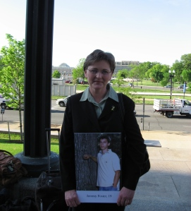 Becky Foster holds a picture of her stepson, Jeremy, who was killed in an auger at a Deltic Timber plant at age 19. Later, Becky testified at a House Education & Labor Committee hearing about OSHA penalties.
